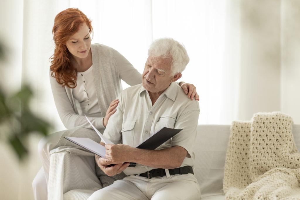 Senior man watching photobook during visit of granddaughter at home